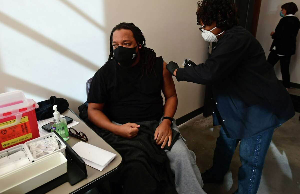 Norwalk Community Healthcare Center nurse Manette Destin administers a COVID-19 vaccine shot to Open Door homeless shelter cook Clarence Percy at the at the Smiloe Life Center in Norwalk on Friday, February 12, 2021.