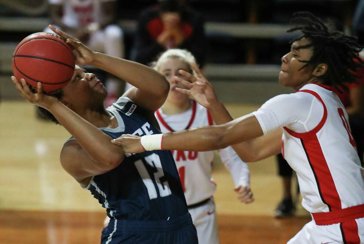 Rice forward India Bellamy (12) is fouled by Western Kentucky guard Myriah Johnson (0) as she takes a shot during the first half of an NCAA women's basketball game on Friday, Feb. 12, 2021, at Tudor Field House in Houston.