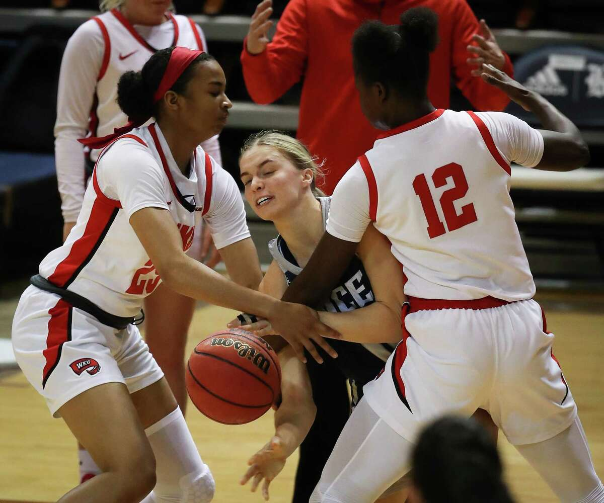 Rice guard Katelyn Crosthwait, center, gets a pass off between Western Kentucky's Jordan Smith (25) and Fatou Pouye (12) during the first half of an NCAA women's basketball game on Friday, Feb. 12, 2021, at Tudor Field House in Houston.