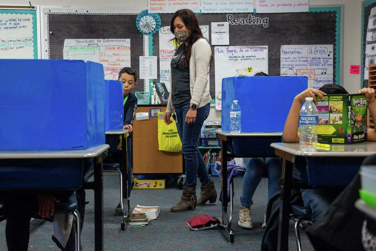 Third grade teacher Yadira Sesher, center, checks in on her students at Calder Road Elementary on Friday, Jan. 15, 2021, in Dickinson, Texas. Tens of thousands of students have opted to return to campuses for instruction despite a surge in COVID-19 infections. In Dickinson ISD, 93 percent of students are back in their classrooms.