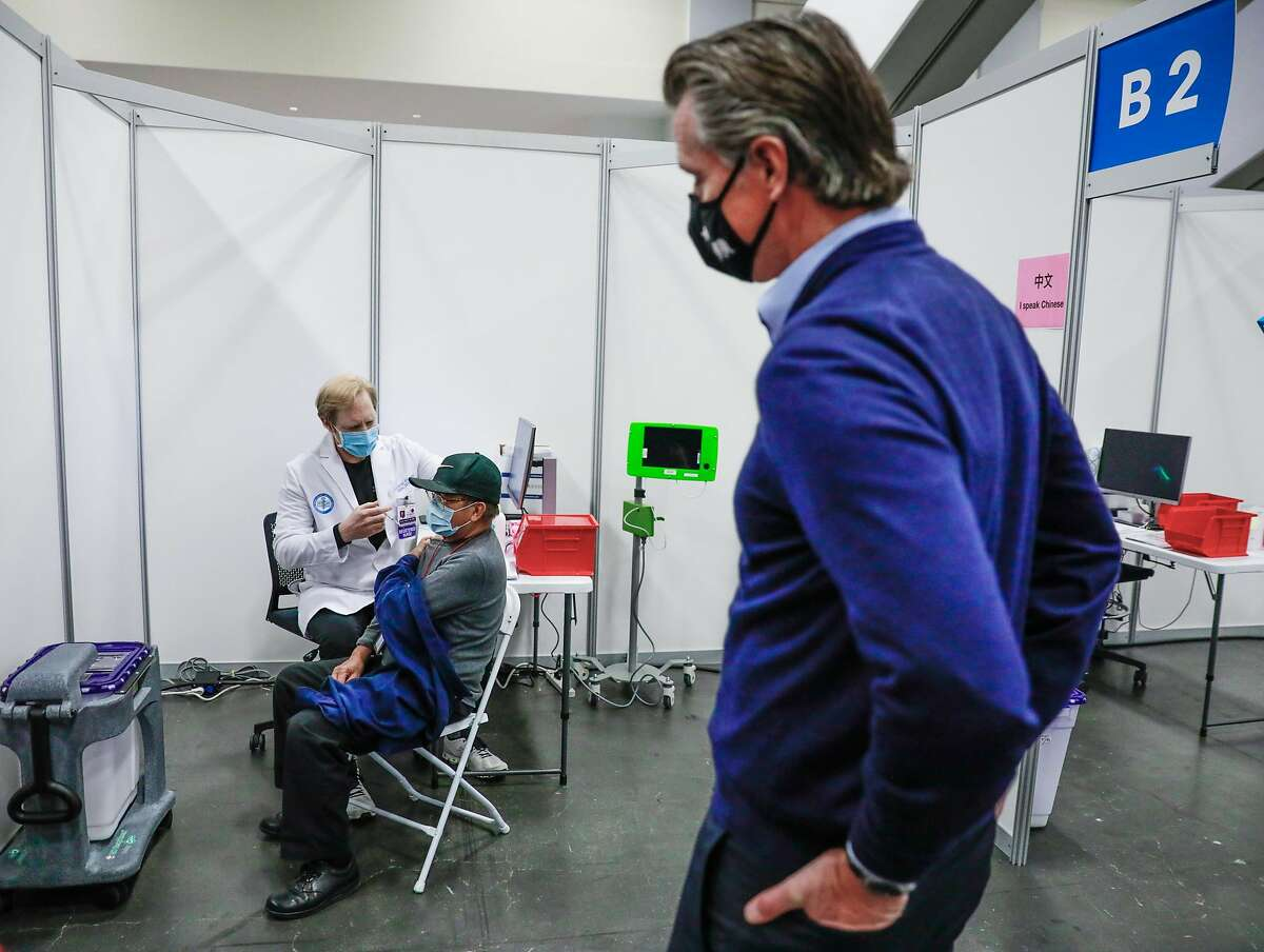 Gov. Gavin Newsom watches as Antonio Rabanal, 73, is vaccinated at the Moscone Center by nurse Scott Keech.