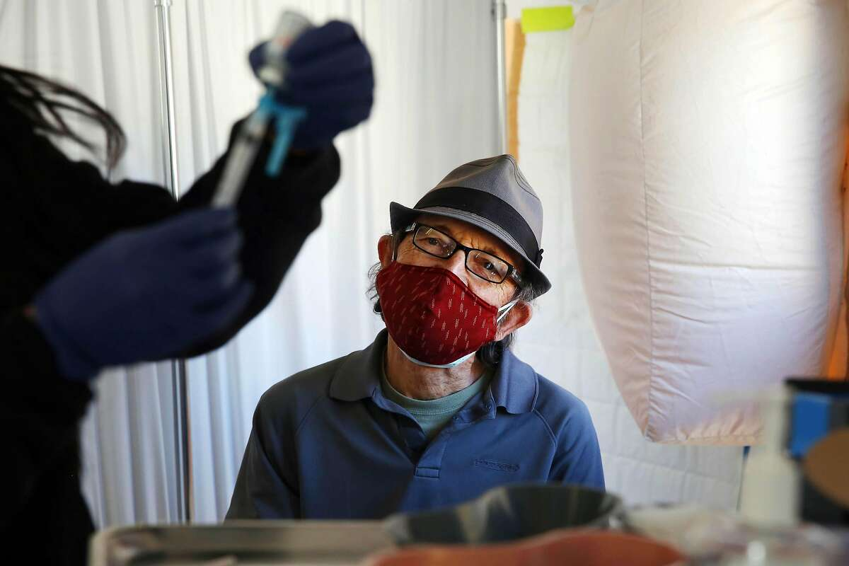 Stephen Haggard watches his vaccine shot being prepped at the Southeast Health Center on Friday, February 12, 2021 in San Francisco, Calif.