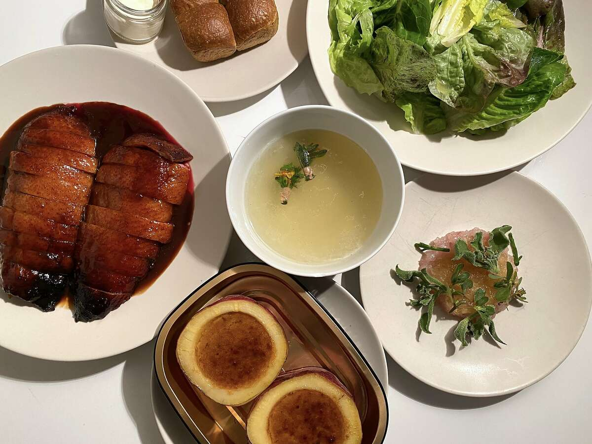 A spread of dishes from Saison's meal kit, featuring aged duck breast, Japanese sweet potato and salad.