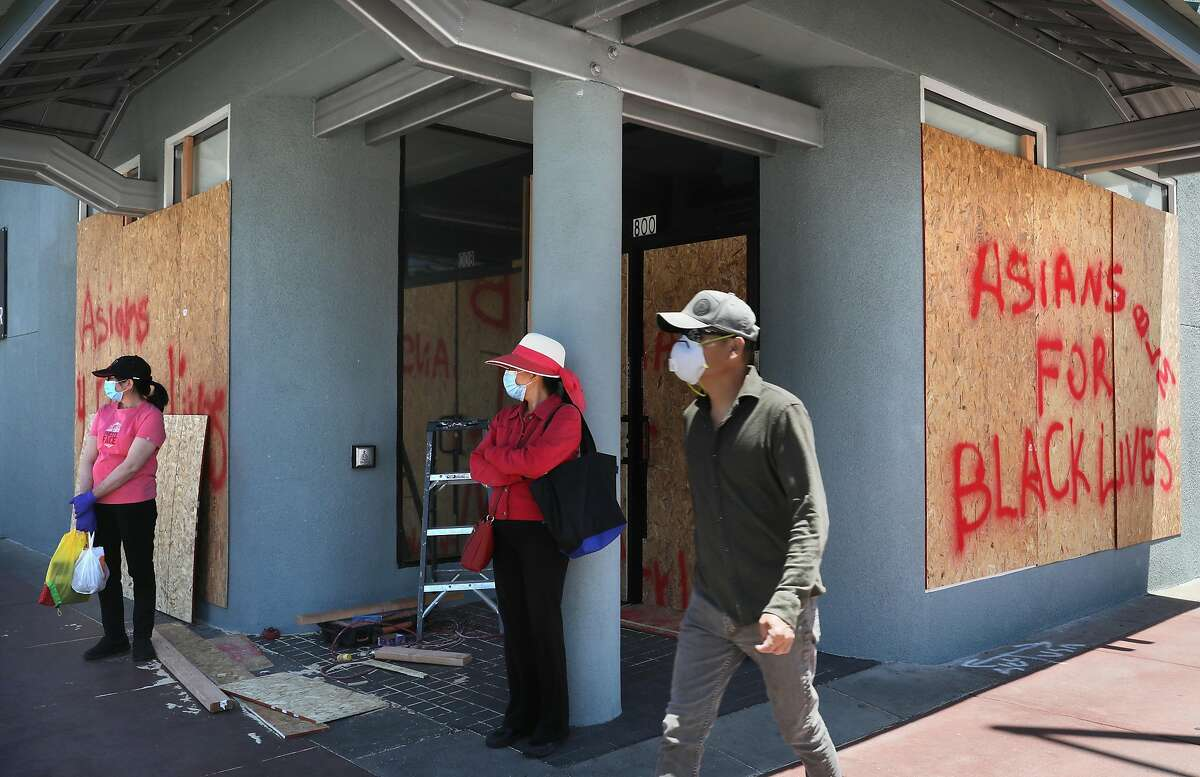 Boards in Oakland's Chinatown last year convey Asian Americans' support for Black Lives Matter. Black community leaders started a fundraiser this month for Asian residents who were victims of violent crimes, raising $15,000 in a few days.