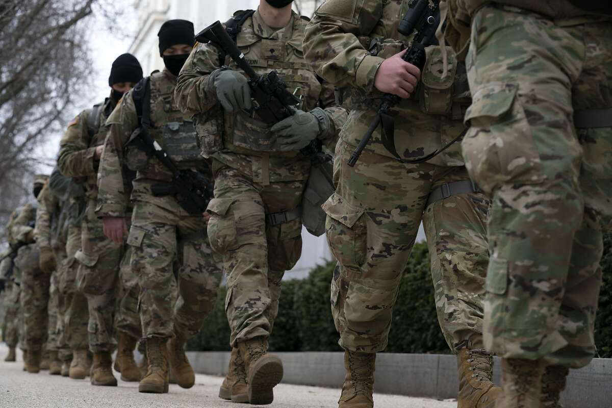 Members of the National Guard march outside of the U.S. Capitol during the impeachment trial of former President Donald Trump at the Capitol in Washington, Friday, Feb. 12, 2021. (AP Photo/Jose Luis Magana)