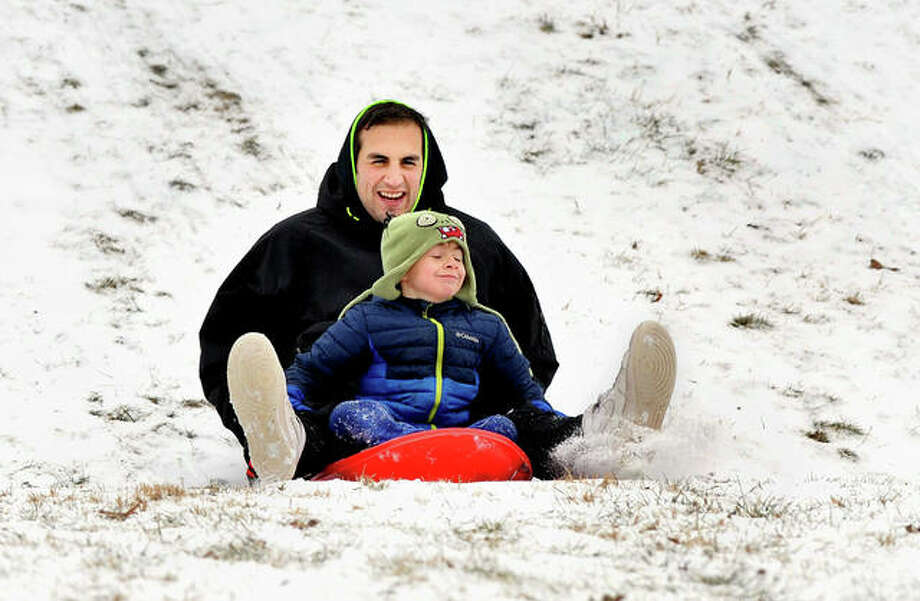 Anthony Pletcher and his son Benjamin, 8, of Glen Carbon, sled down a hill at Miner Park in Glen Carbon Thursday ahead of snowy weather and low temperatures expected by Tuesday. Photo: Thomas J. Turney | For The Intelligencer