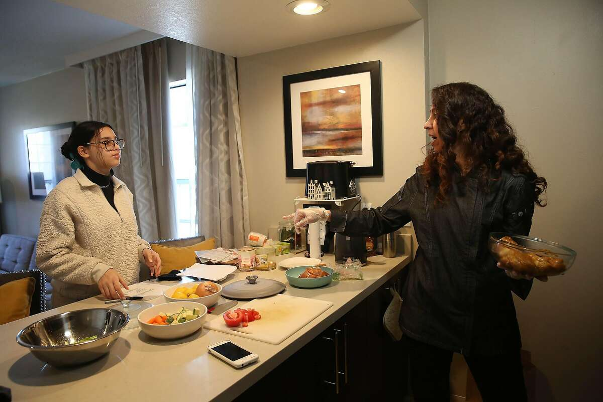 Shereen Hassan-Aly (right) talks with her daughter Heba Hadi (left) as she cooks in a space she uses as a test kitchen and Hadi writes personalized notes for customized packaging on orders in a space she uses as a test kitchen on Friday, February 12, 2021 in Newark, Calif.