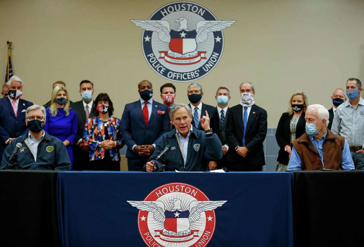 """Gov. Greg Abbott, center, talks to reporters during a press conference inside the Houston Police Officer's Union Headquarters, where he signed a """"back the blue"""" pledge Wednesday, Oct. 28, 2020, in Houston."""