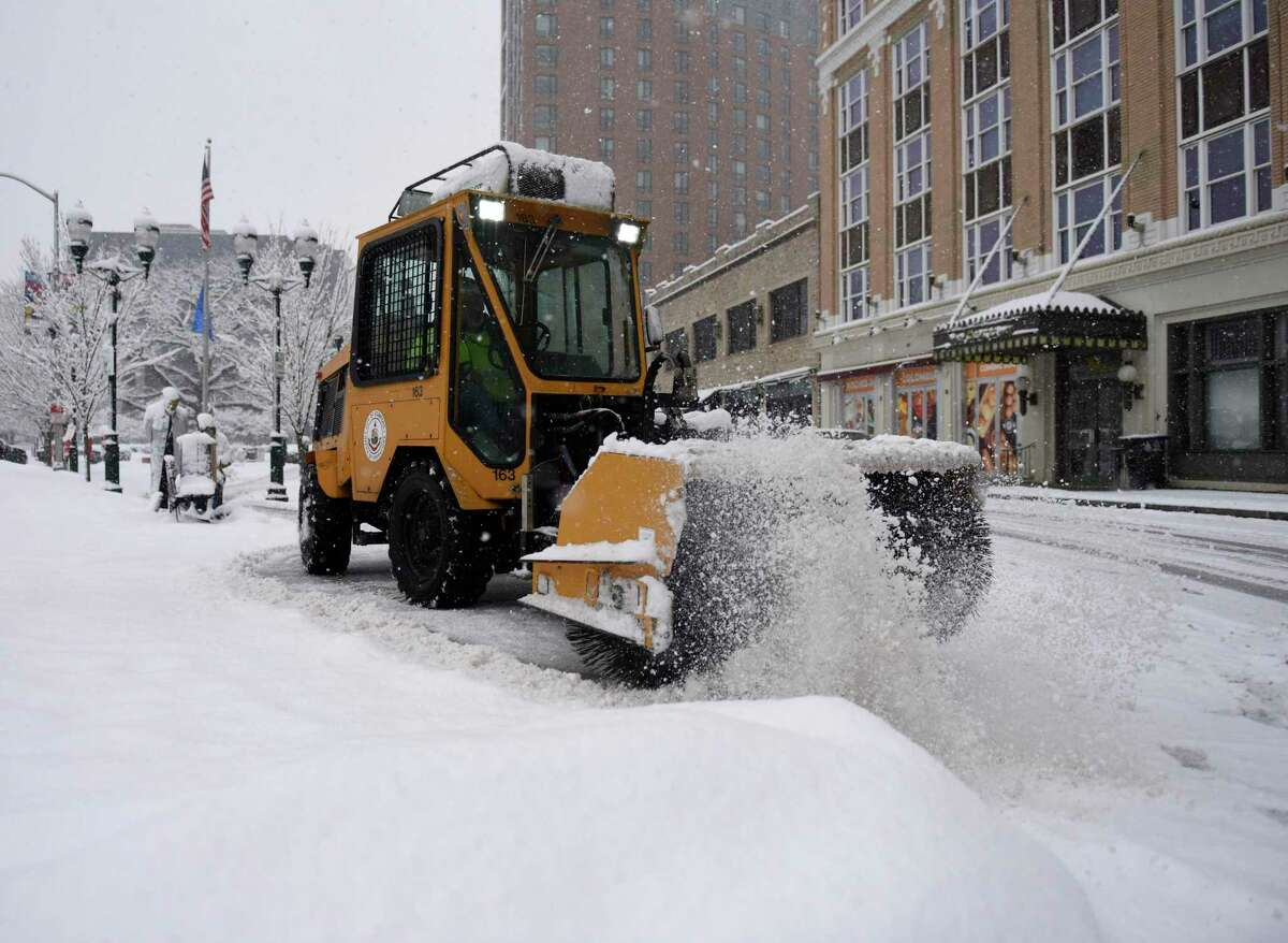 A plow removes snow from the sidewalk at Columbus Park in Stamford, Conn. Sunday, Feb. 7, 2021.