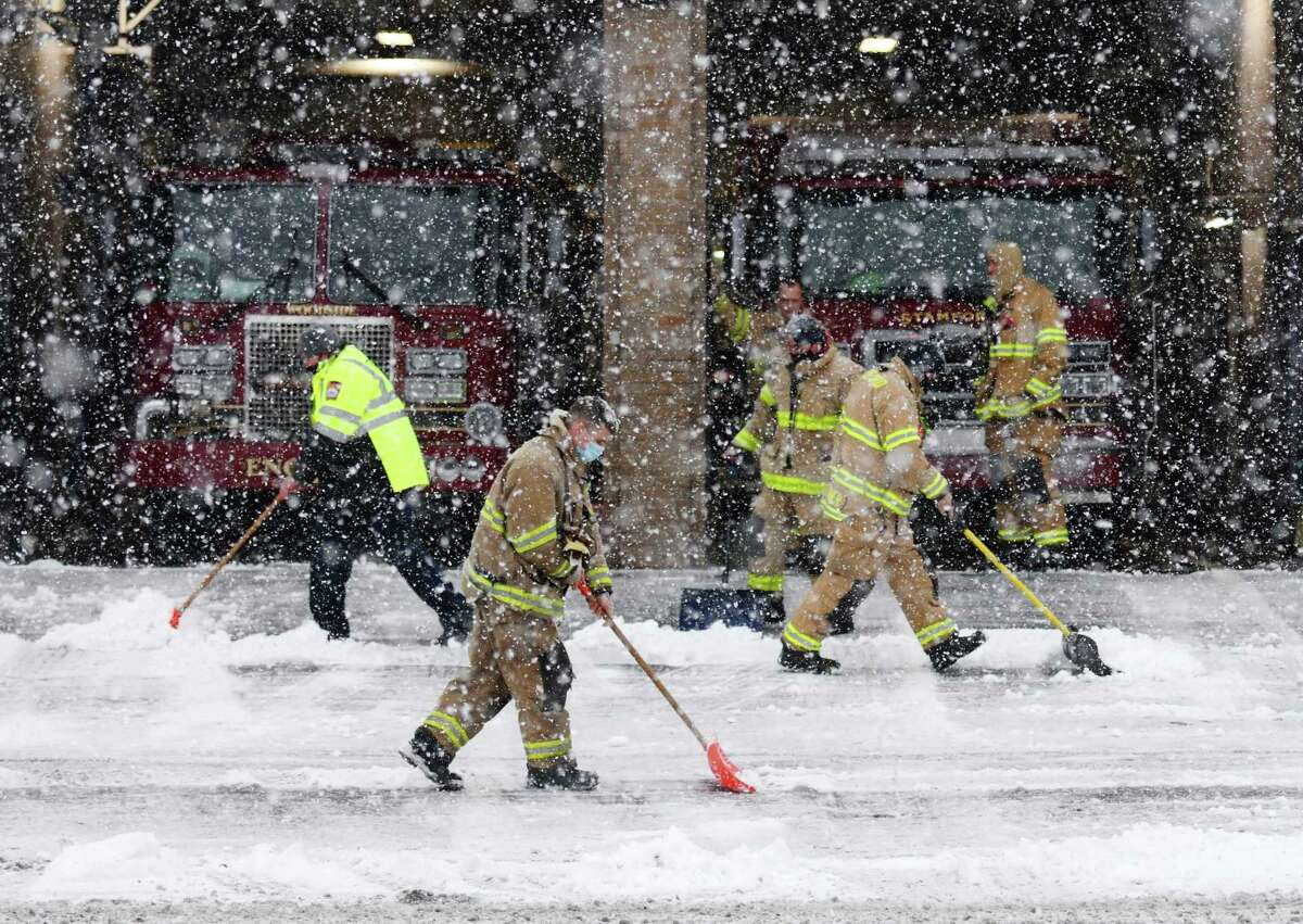 Firefighters shovel the drive at the Woodside Firehouse in Stamford, Conn. Sunday, Feb. 7, 2021.