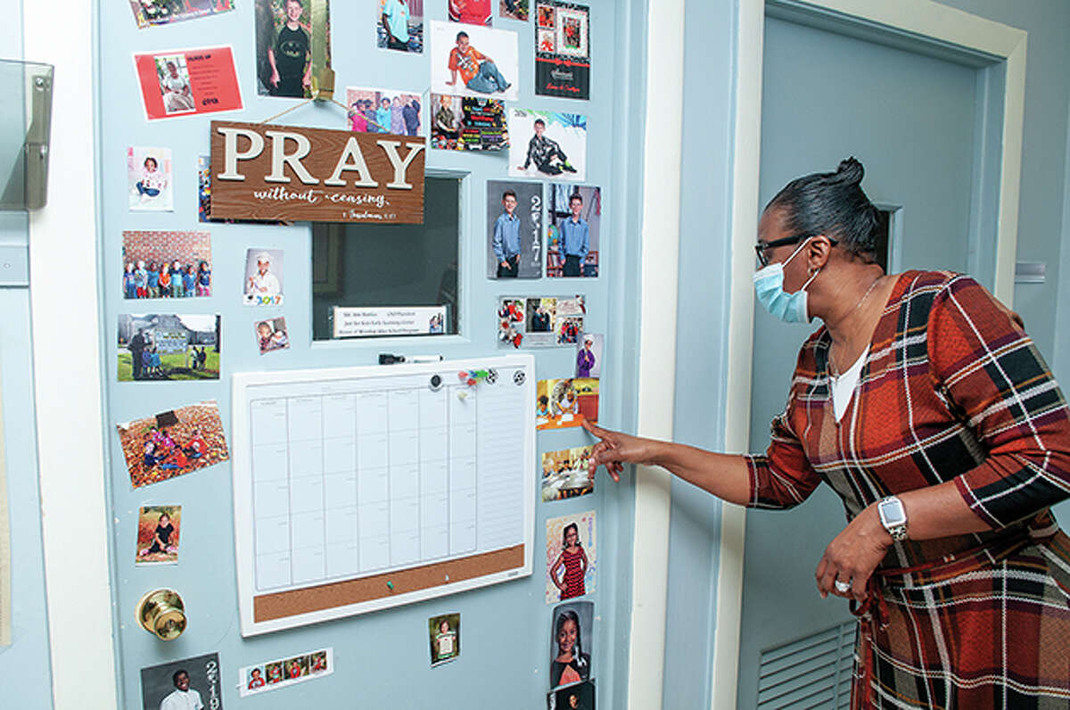 Ann Burries points to one of many photos on an office door at Just for Kids Early Learning Center. The photos are of families and children who have been part of the learning center's history.