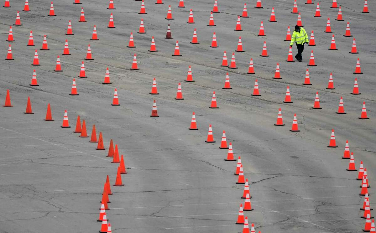 A worker arranges cones at a mostly-empty vaccination site at Dodger Stadium on Thursday in Los Angeles. A nationwide shortage of COVID-19 vaccines is hindering efforts to vaccinate residents of California and other states. (AP Photo/Marcio Jose Sanchez)