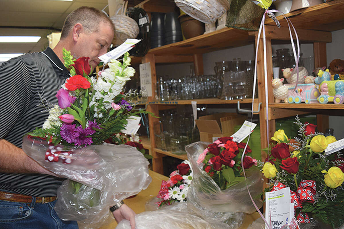 Brian Chumley packages bouquets of flowers Friday at All Occasions Flowers and Gifts in preparation for the Valentine's Day rush.