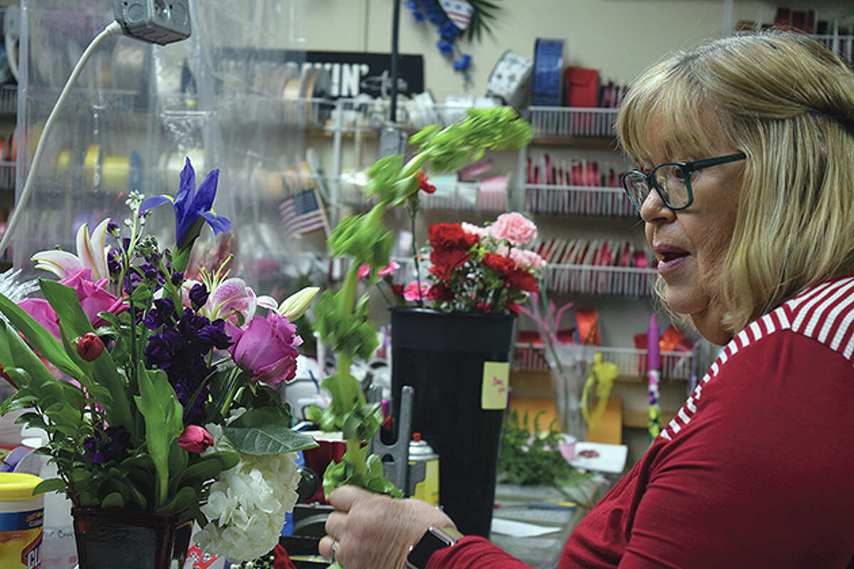 JoAnn Chumley prepares a flower bouquet Friday at All Occassions Flowers and Gifts.