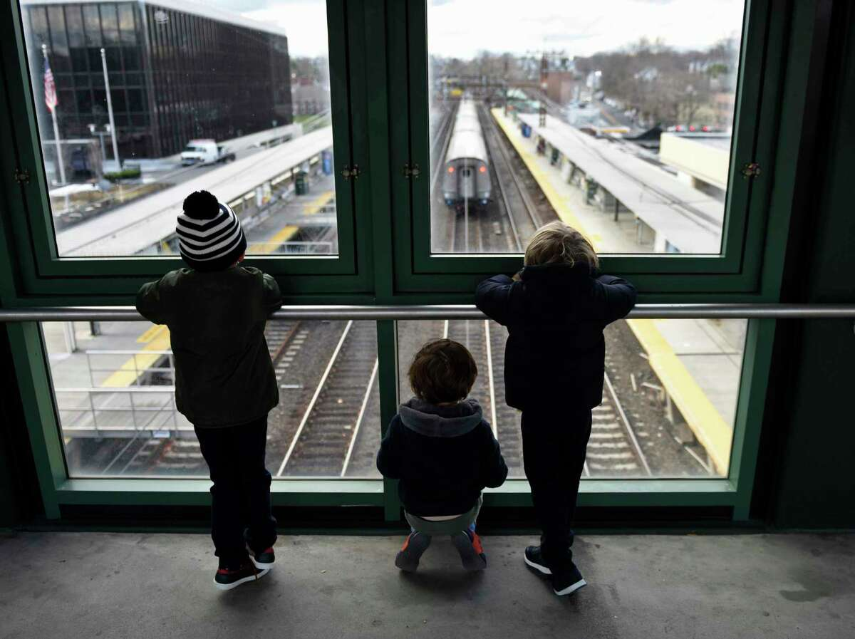 A group of kids excitedly watch as a train passes through the Metro-North station in Greenwich, Conn. on Tuesday, Dec. 1, 2020. New Haven Line ridership is down 80 percent during the COVID crisis.