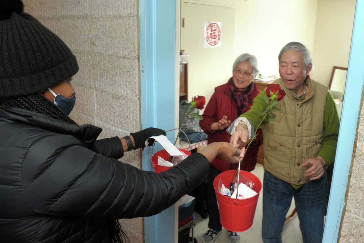 Vanessa Cardinal, a social worker with Community Centers Inc., delivers Valentine's Day sweets and roses to Agnes Morley Heights residents Qian Naiyo, center, and Zhong Xingchu, right, in Greenwich, Conn. Feb. 12, 2021.