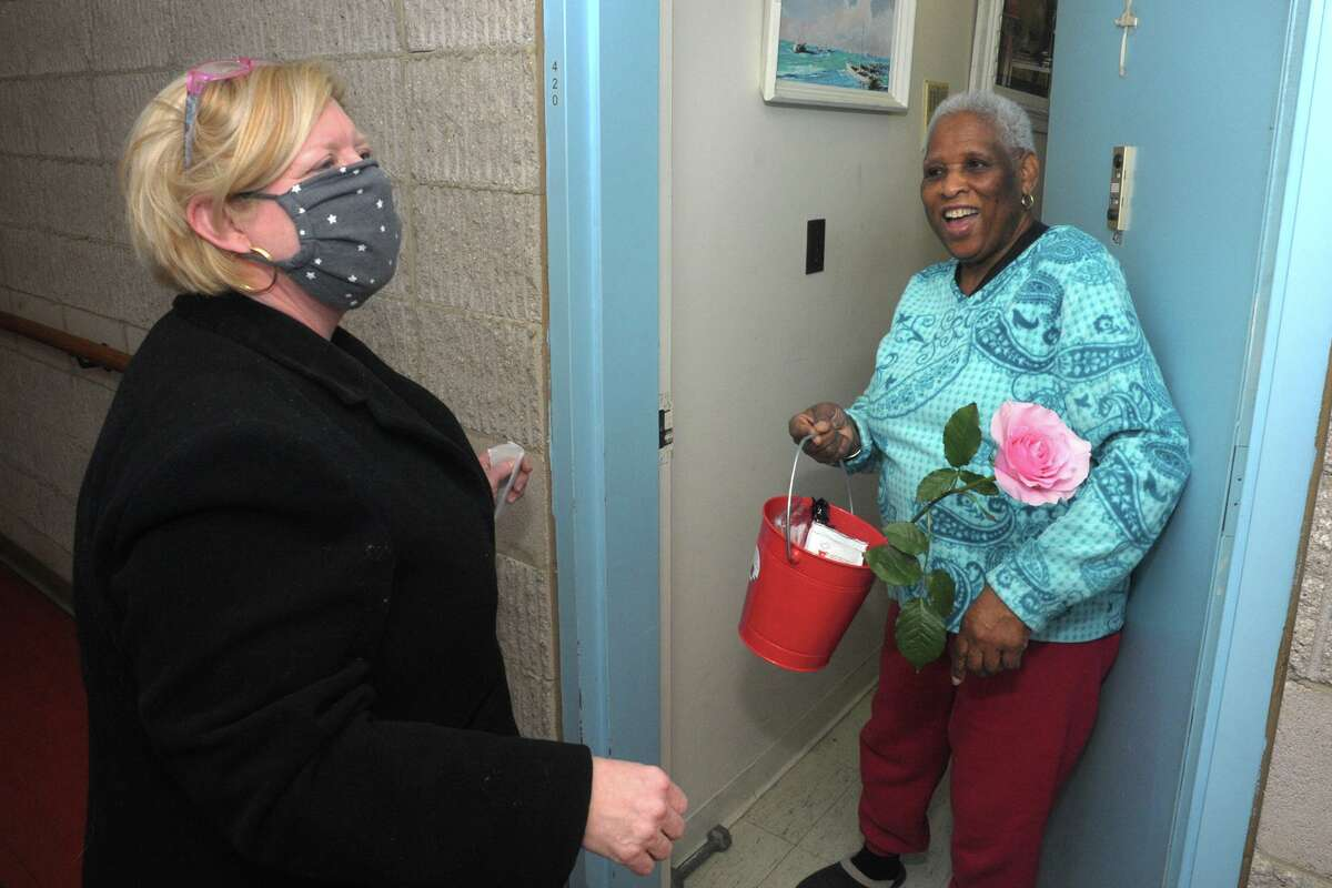 Le Ann Hinkle, a volunteer with Community Centers Inc., delivers Valentine's Day sweets and roses to Agnes Morley Heights resident Myrna Marsh in Greenwich, Conn. Feb. 12, 2021.