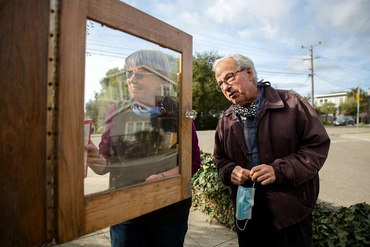 John Culver and Janine Bajus check out a Berkeley free library.