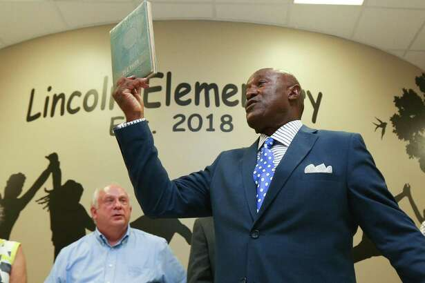 Montgomery City Councilman TJ Wilkerson, who graduated from the original Lincoln High School, holds up his yearbook during the grand opening for Lincoln Elementary School on Tuesday, Aug. 7, 2018, in Montgomery.
