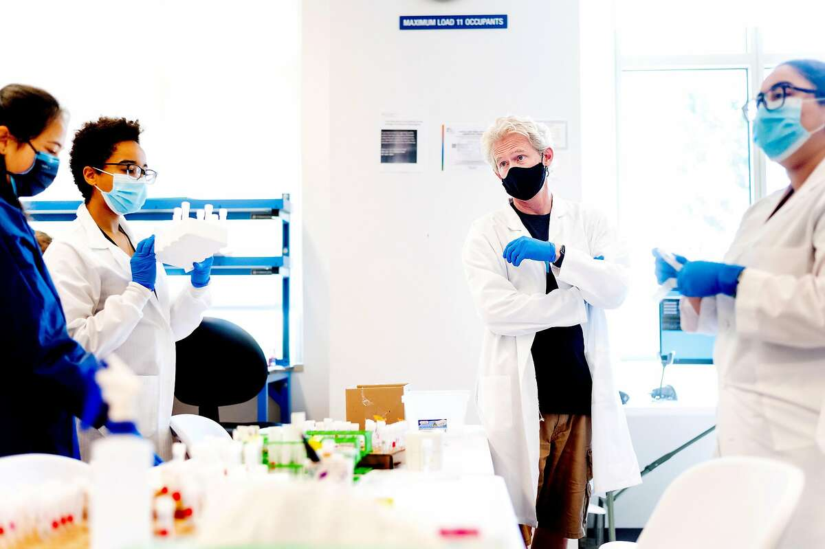 Joe DeRisi, professor of biochemistry and biophysics at UCSF, speaks with scientists as they process coronavirus test samples at a new UCSF diagnostic laboratory adjacent to the Chan Zuckerberg Biohub in April.