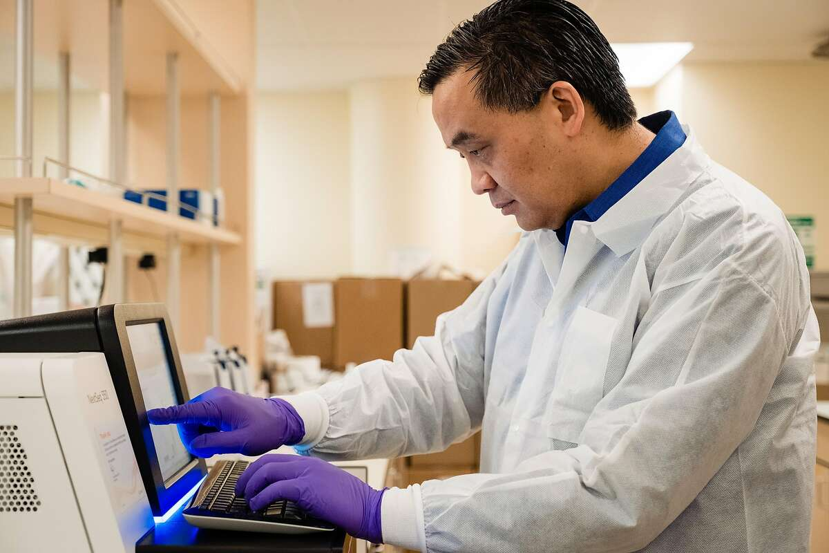 Microbiologist Dr. Charles Chiu checks on a system to sequence coronavirus genomes in San Francisco in March.