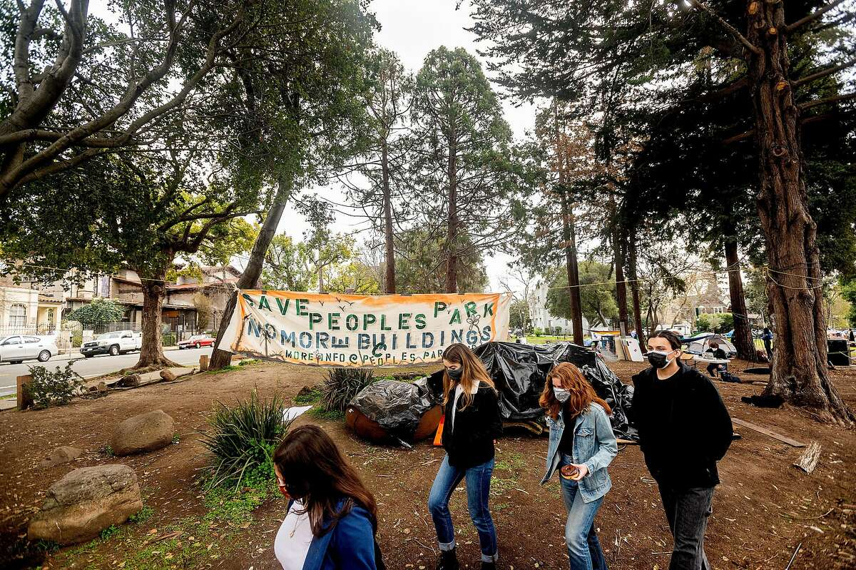 Students walk past a protest banner at People's Park, where UC Berkeley plans housing for students and homeless people.