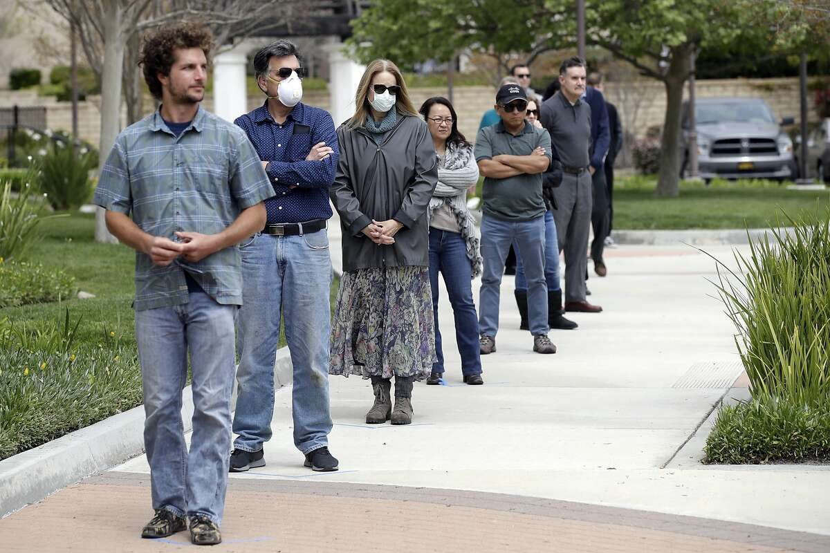 Socially distanced worshipers line up outside a church in Ventura County.