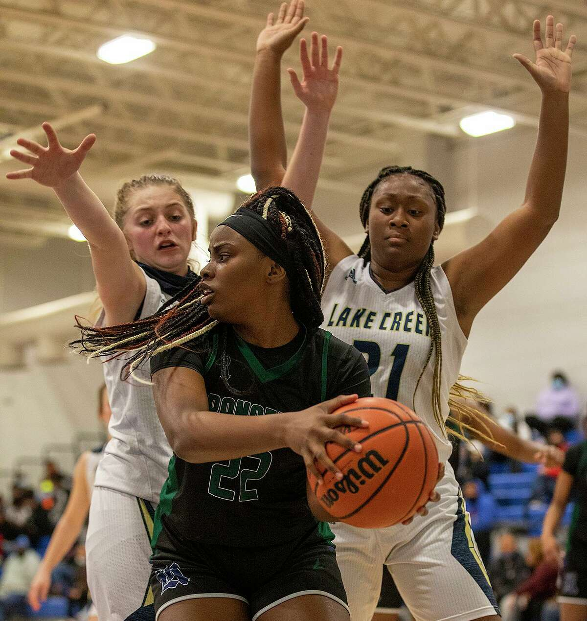 Rudder's Cameron Richards (22) looks for room around Montgomery Lake Creek's Indy Lovelady (21) and Makenzie Logeman (1) during game action of a bi-district playoff at Navasota High School on Friday, Feb. 12, 2021.