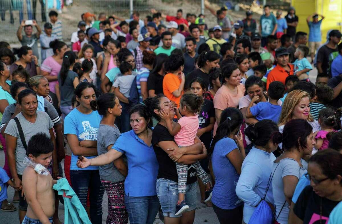 En esta imagen de archivo del 30 de agosto de 2019, migrantes, muchos de ellos devueltos a México por la política migratoria del entonces presidente estadounidense Donald Trump, hacen fila para recibir alimentos en un campamento en el puente internacional, en Matamoros, México.
