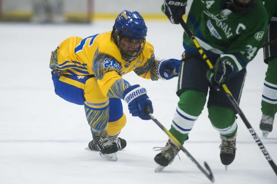Matthew Witt reaches for the puck during Wednesday's game against Saginaw Heritage. Photo: Daily News File Photo