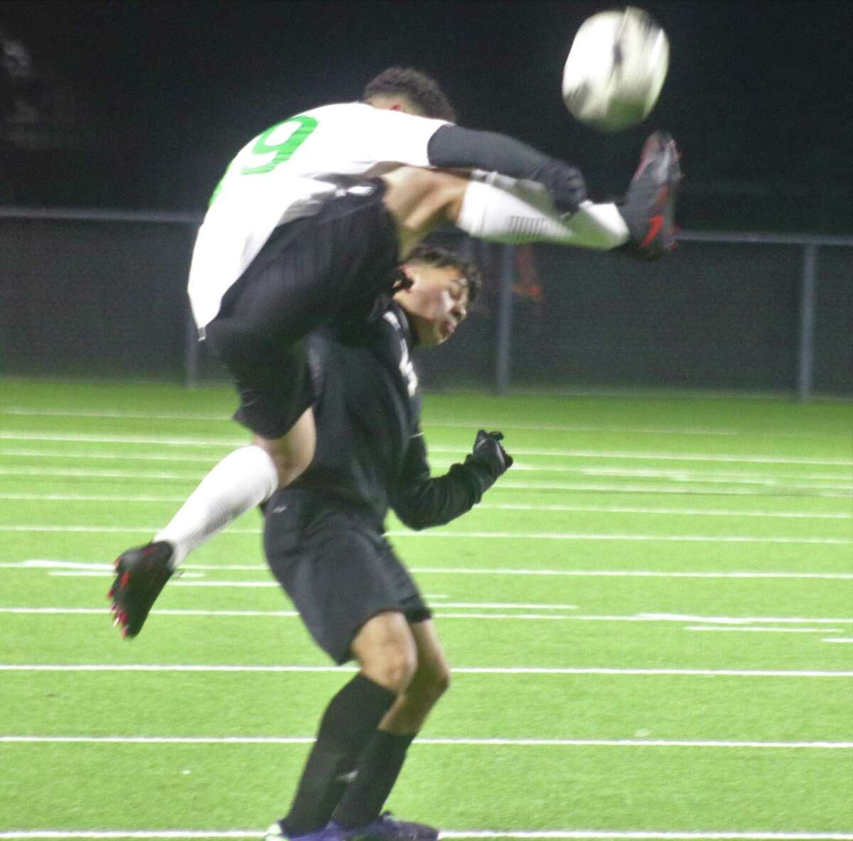 An Eagles player takes to the air in order to kick the ball away from a Memorial player during first-half action at frigid Veterans Memorial Stadium Friday night.