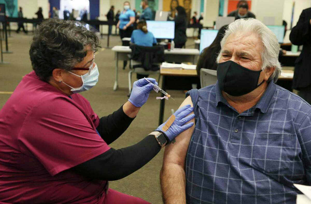 Hank Cortez, right, receives the Pfizer vaccine from University Health's Edna Fuster on Feb. 12, 2021, at the vaccination center set up inside Wonderland of the Americas mall. Since it started vaccinating people for the coronavirus about two months ago, University Health said it has not lost a single dose.