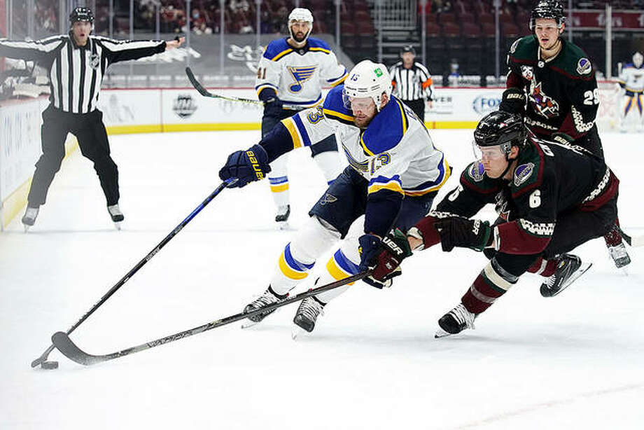 Blues left wing Kyle Clifford (13) shields Arizona defenseman Jakob Chychrun (6) from the puck Friday night in Glendale, Ariz.