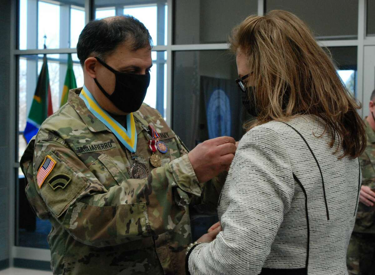 New York Army National Guard Lt. Col. Michael Tagliafierro pins a Family Recognition Award pin on his wife Maureen during his retirement ceremony.