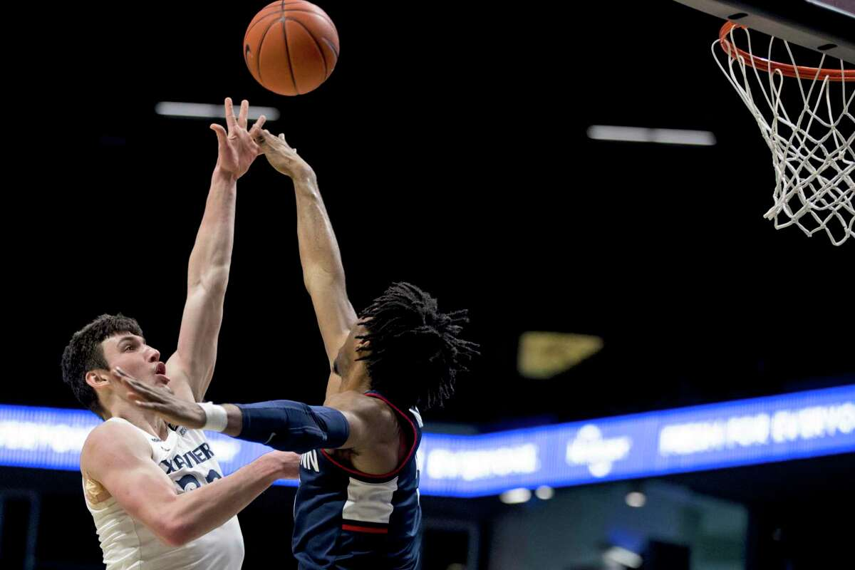 Xavier forward Zach Freemantle (32) shoots over Connecticut forward Isaiah Whaley (5) in the first half of an NCAA college basketball game, Saturday, Feb. 13, 2021, in Cincinnati. (Albert Cesare/The Cincinnati Enquirer via AP)