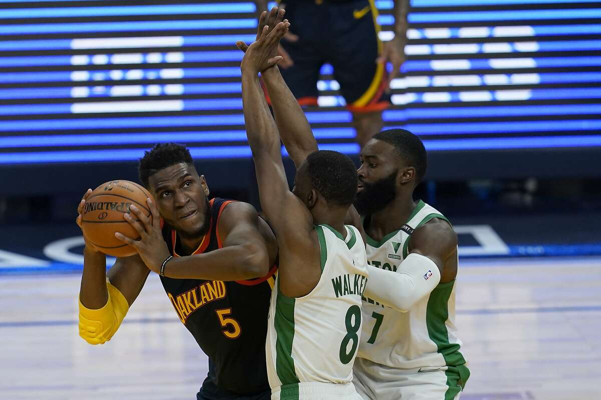Golden State Warriors forward Kevon Looney (5) is defended by Boston Celtics guard Kemba Walker (8) and guard Jaylen Brown (7) during an NBA basketball game in San Francisco, Tuesday, Feb. 2, 2021. (AP Photo/Jeff Chiu)