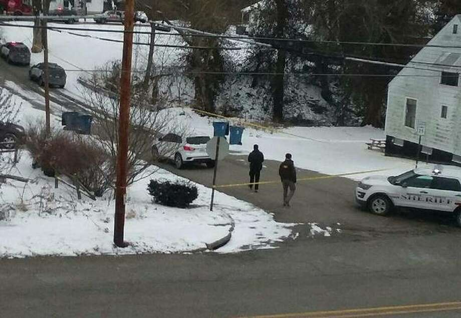 Alton Police and Madison County Sheriff's Department deputies examine an area around 11th and Alby streets Saturday afternoon after reports of gunfire. Police said one person is dead and one person is being detained in connection to the shooting.