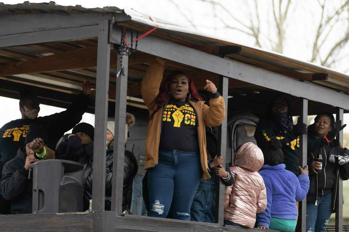 Parade participants raise their fists in the air during Conroe's annual Black History Parade, Saturday, Feb. 13, 2021, near downtown Conroe. The parade started near the Conroe library and concluded at Booker T. Washington High School with an award presentation.