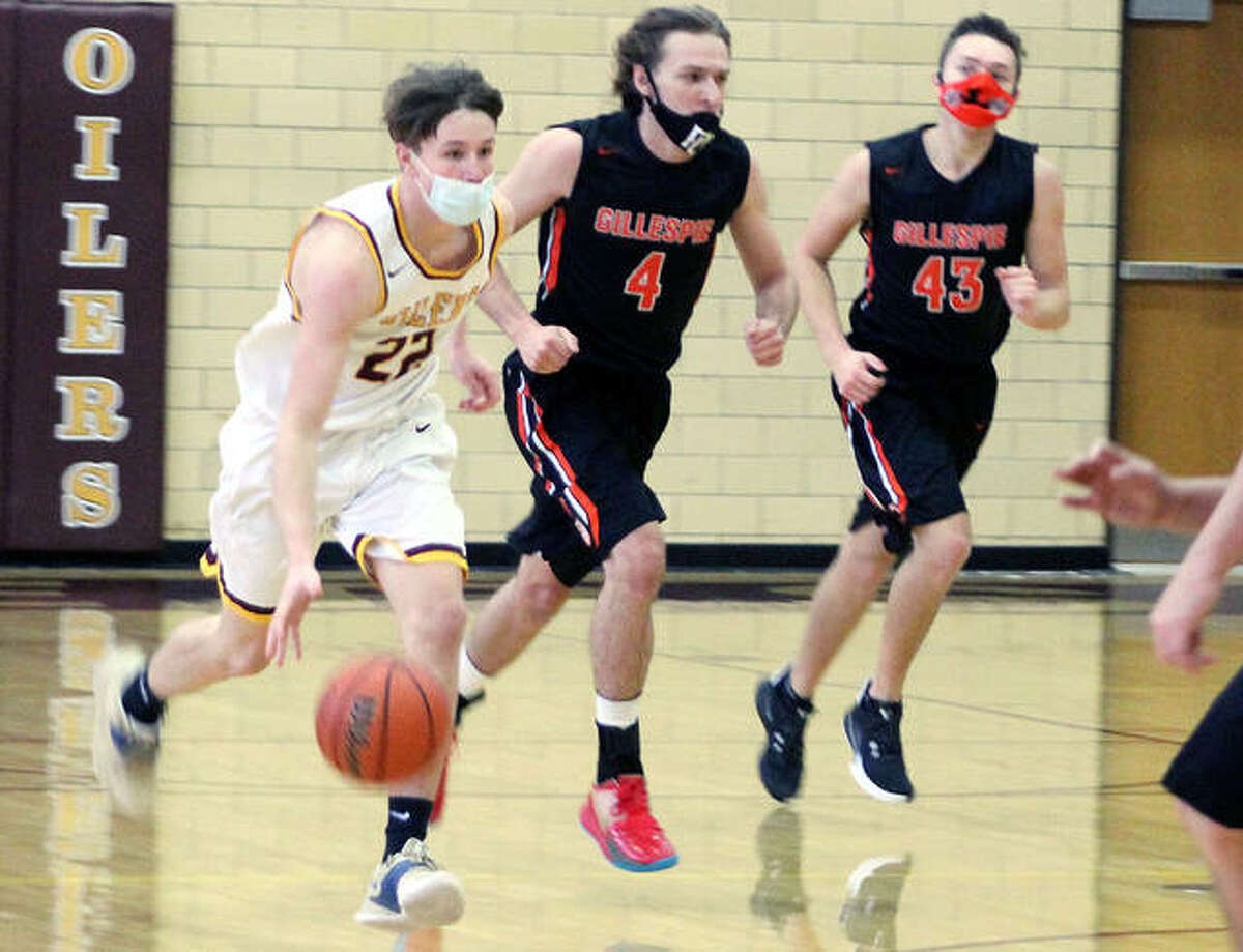 EA-WR sophomore Seth Slayden (22) brings the ball upcourt trailed by Giillespie's Anthony Rives (4) and Jack Herron (43) during Saturday's game in Wood River.