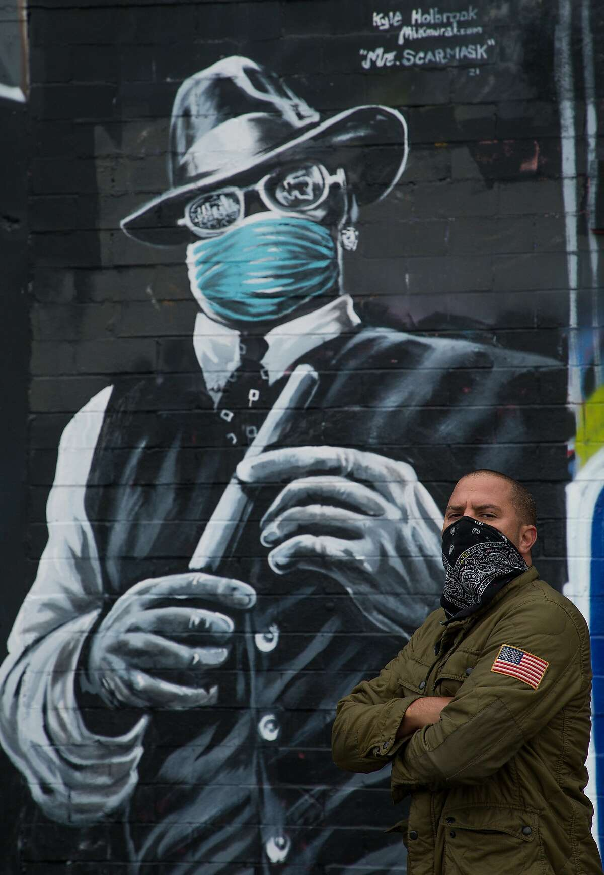 Kyle Holbrook poses for a photograph with his mural of Mr. Scarface on Thursday, Feb. 11, 2021, in EaDo, Houston. Holbrook said he decided to have the legendary Houston rapper wearing a face mask as a reminder for Houstonians and visitors to wear masks.