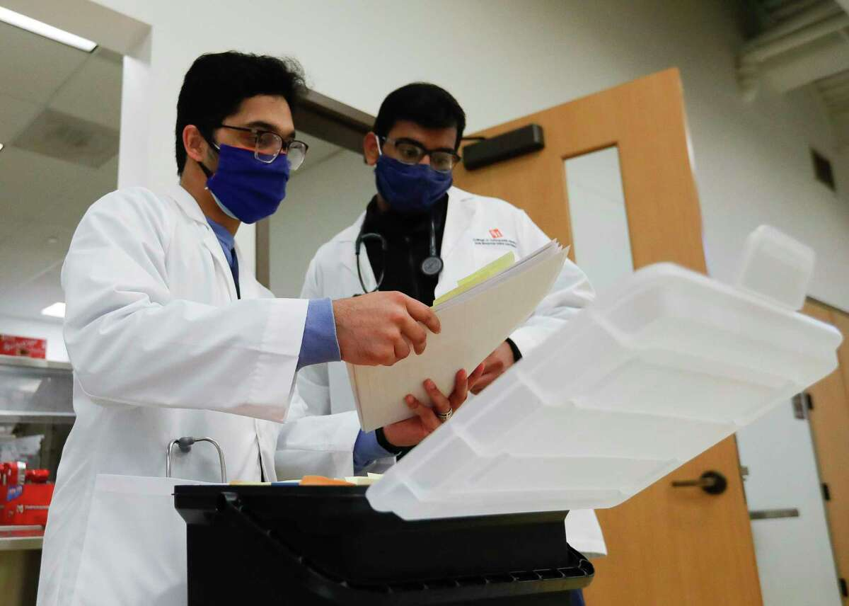 Medical student Alwyn Mathew, left, and Amir Rashee look over paperwork as students with Sam Houston State University's College of Osteopathic Medicine administered healthcare to community members at the Conroe Salvation Army, Saturday, Feb. 13, 2021, in Conroe.