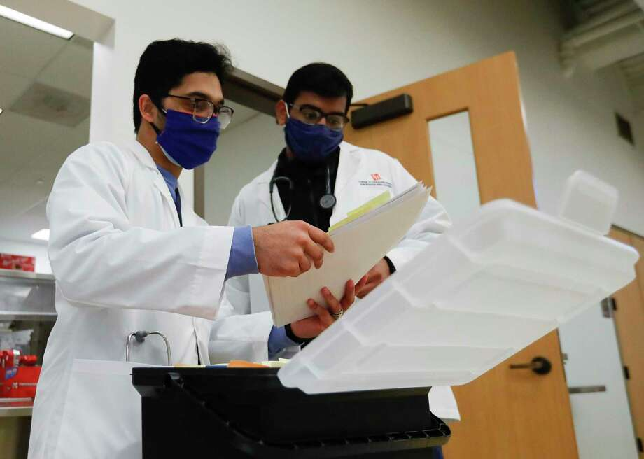 Medical student Alwyn Mathew, left, and Amir Rashee look over paperwork as students with Sam Houston State University's College of Osteopathic Medicine administered healthcare to community members at the Conroe Salvation Army, Saturday, Feb. 13, 2021, in Conroe. Photo: Jason Fochtman, Houston Chronicle / Staff Photographer / 2021 © Houston Chronicle