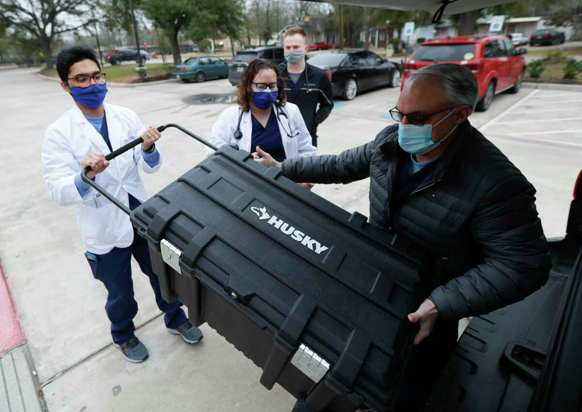 Medical student Alwyn Mathew, left, helps Doctor Craig Boudreaux unlopad supplies as students with Sam Houston State University's College of Osteopathic Medicine administered healthcare to community members at the Conroe Salvation Army, Saturday, Feb. 13, 2021, in Conroe.
