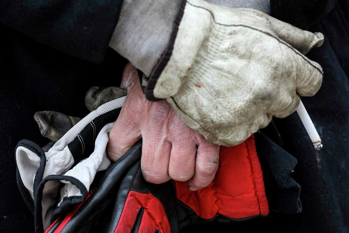 A man holds new gloves given to him by members of the Harris County Sheriff's Office Homeless Outreach Team ahead of a winter storm Saturday, Feb. 13, 2021, behind a Best Buy on I-45 in Houston. The deputies handed out cold weather items and offered assistance.