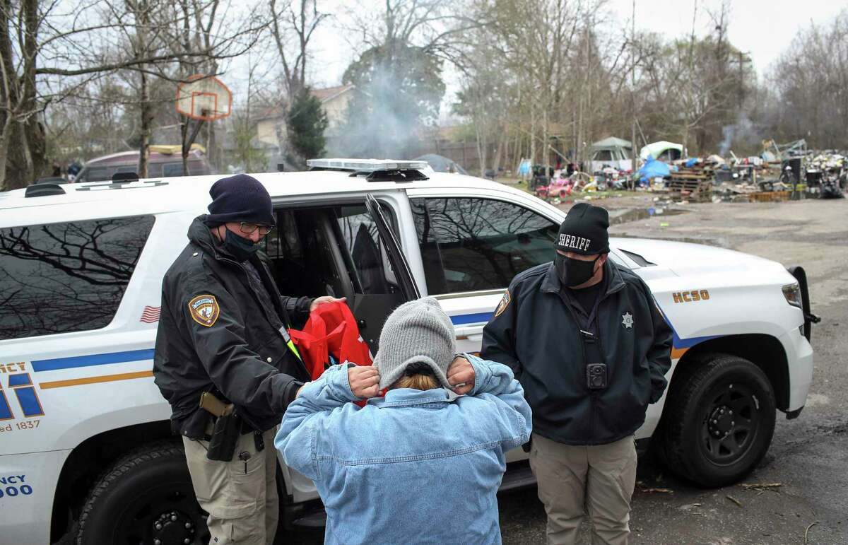 Harris County Deputy Sheriffs James Kelley, left, and Jason Dean, give a woman a beanie ahead of a winter storm Saturday, Feb. 13, 2021, in Harris County. The woman and several others lived in the lot, and the Homeless Outreach Team handed out cold-weather items and offered assistance.