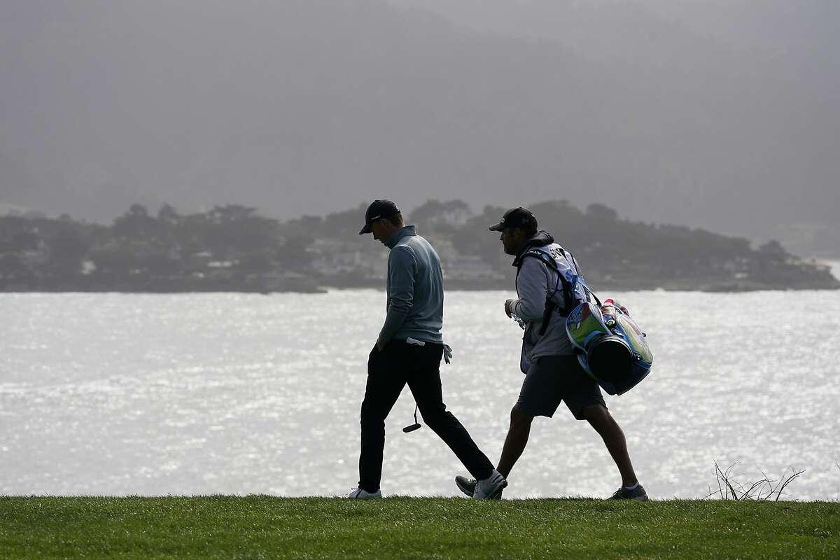 Jordan Spieth, left, walks down the eighth fairway of the Pebble Beach Golf Links during the third round of the AT&T Pebble Beach Pro-Am golf tournament Saturday, Feb. 13, 2021, in Pebble Beach, Calif. (AP Photo/Eric Risberg)