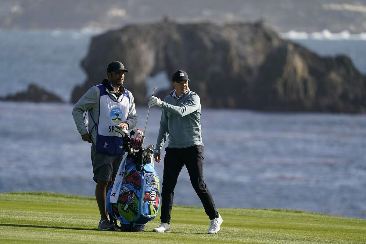 Jordan Spieth puts a club back in his bag after hitting from the 18th fairway of the Pebble Beach Golf Links during the third round of the AT&T Pebble Beach Pro-Am golf tournament Saturday, Feb. 13, 2021, in Pebble Beach, Calif. (AP Photo/Eric Risberg)