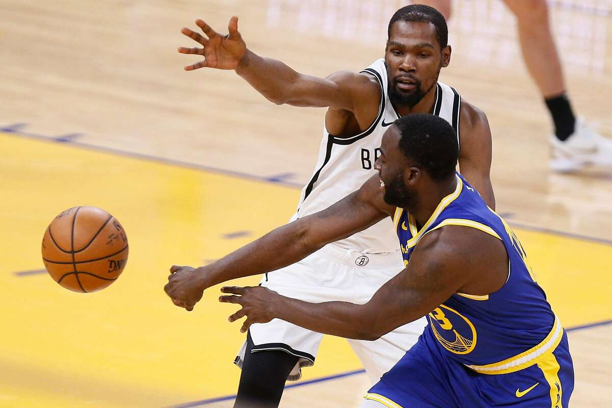 Golden State Warriors forward Draymond Green (23) passes while defended by Brooklyn Nets forward Kevin Durant (7) in the first quarter of an NBA game at Chase Center, Saturday, Feb. 13, 2021, in San Francisco, Calif.