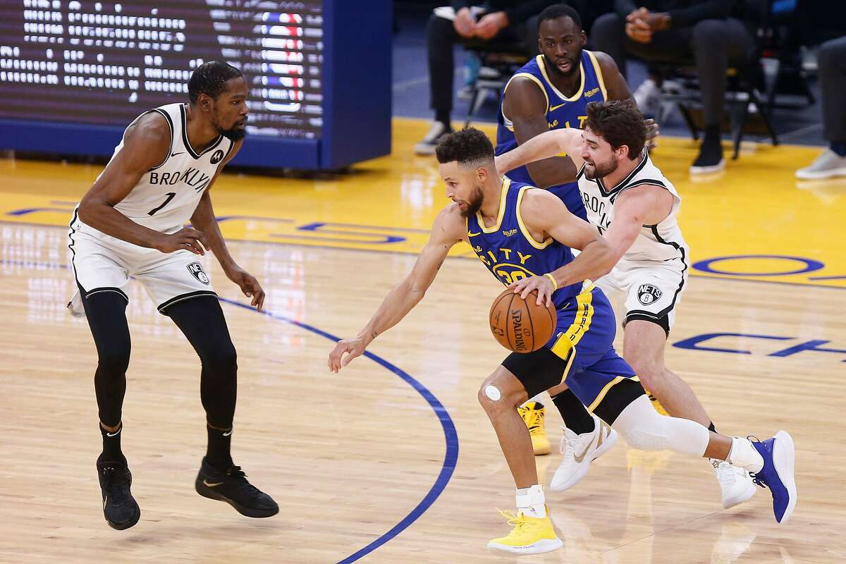 Golden State Warriors guard Stephen Curry (30) drives to the hoop against Brooklyn Nets forward Kevin Durant (7) in the first quarter of an NBA game at Chase Center, Saturday, Feb. 13, 2021, in San Francisco, Calif.