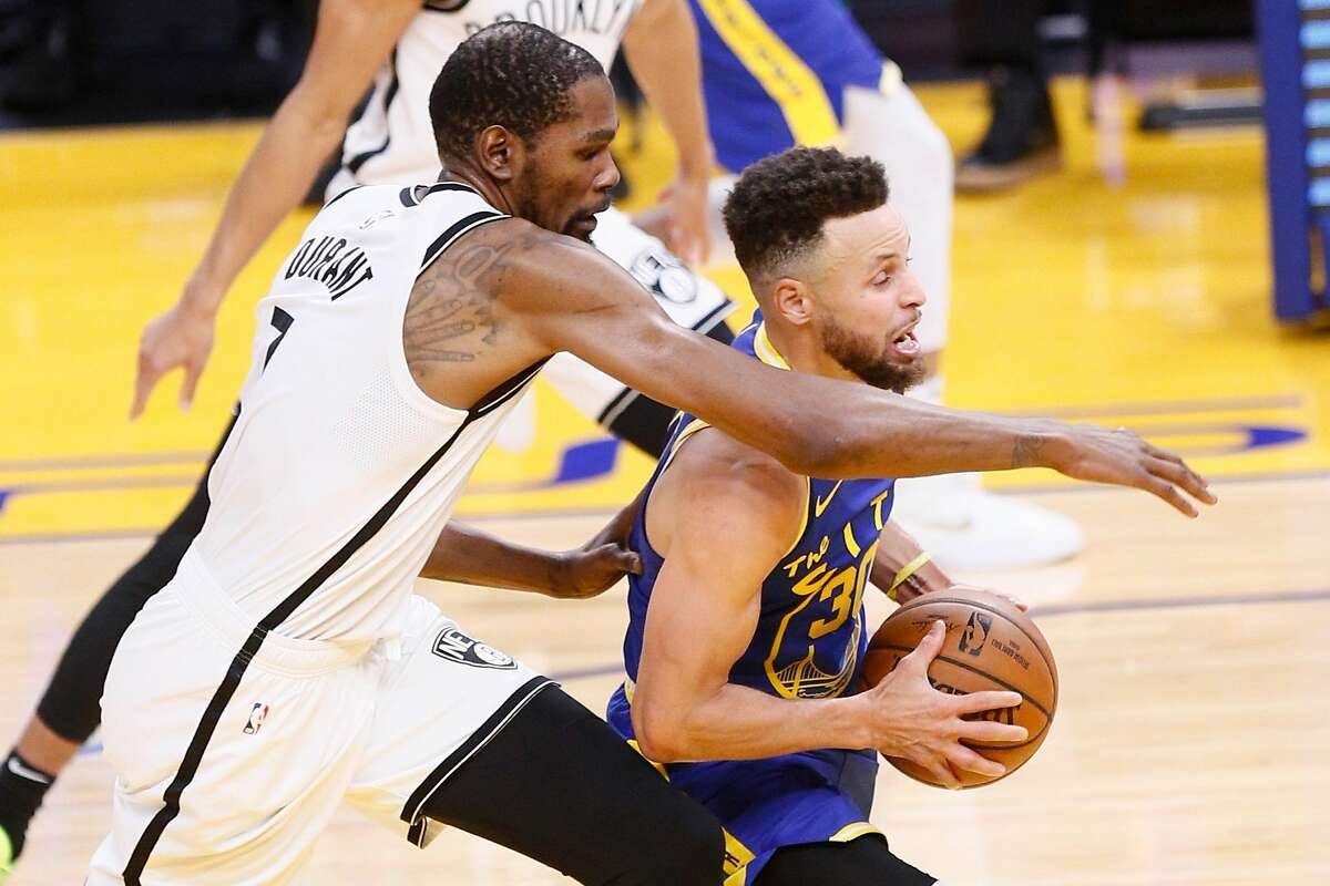 Golden State Warriors guard Stephen Curry (30) drives to the hoop defended by Brooklyn Nets forward Kevin Durant (7) in the third quarter of an NBA game at Chase Center, Saturday, Feb. 13, 2021, in San Francisco, Calif.